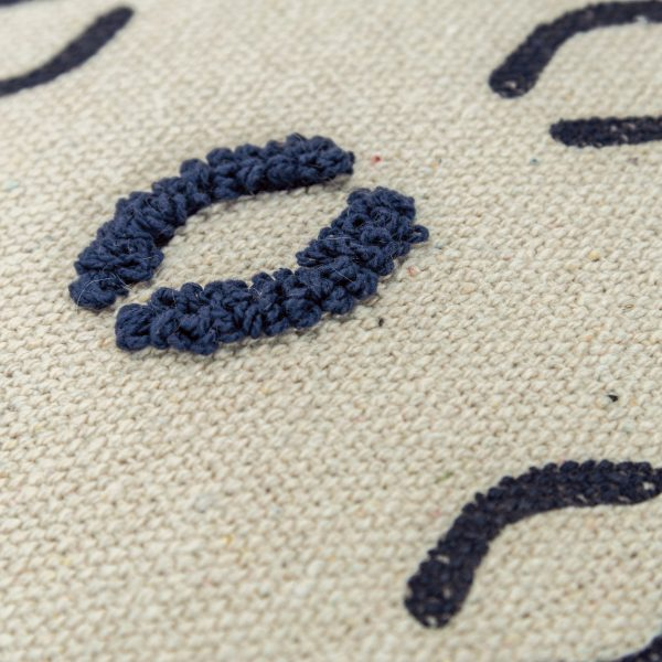 Close up of navy threading detail on textured throw pillow