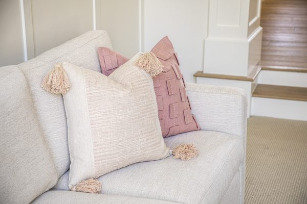 Pink accented throw pillows resting on modern couch