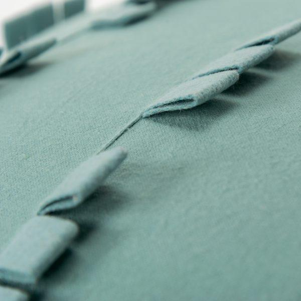 Close up of felt look detail on blue throw pillow