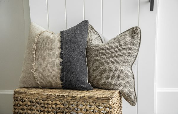 Dylan square pillow and Coronado decorative pillow resting on wicker basket